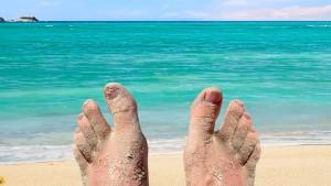 sandige Zehen einer Person am Strand